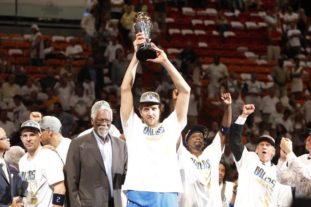 Dallas Mavericks power forward Dirk Nowitzki (41) hoists the Bill Russell NBA Finals MVP Trophy after beating the Miami Heat in game six for the NBA Finals title at American Airlines Arena Sunday, June 12, 2011 in Miami. Mavs won 105-95 (Tom Fox/The Dallas Morning News) To the left is NBA legend Bill Russell who the trophy is named for