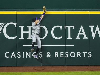 Colorado Rockies left fielder Garrett Hampson makes a leaping play at the wall to rob Texas Rangers outfielder Shin-Soo Choo of a leadoff home run during the first inning at Globe Life Field on Saturday, July 25, 2020.