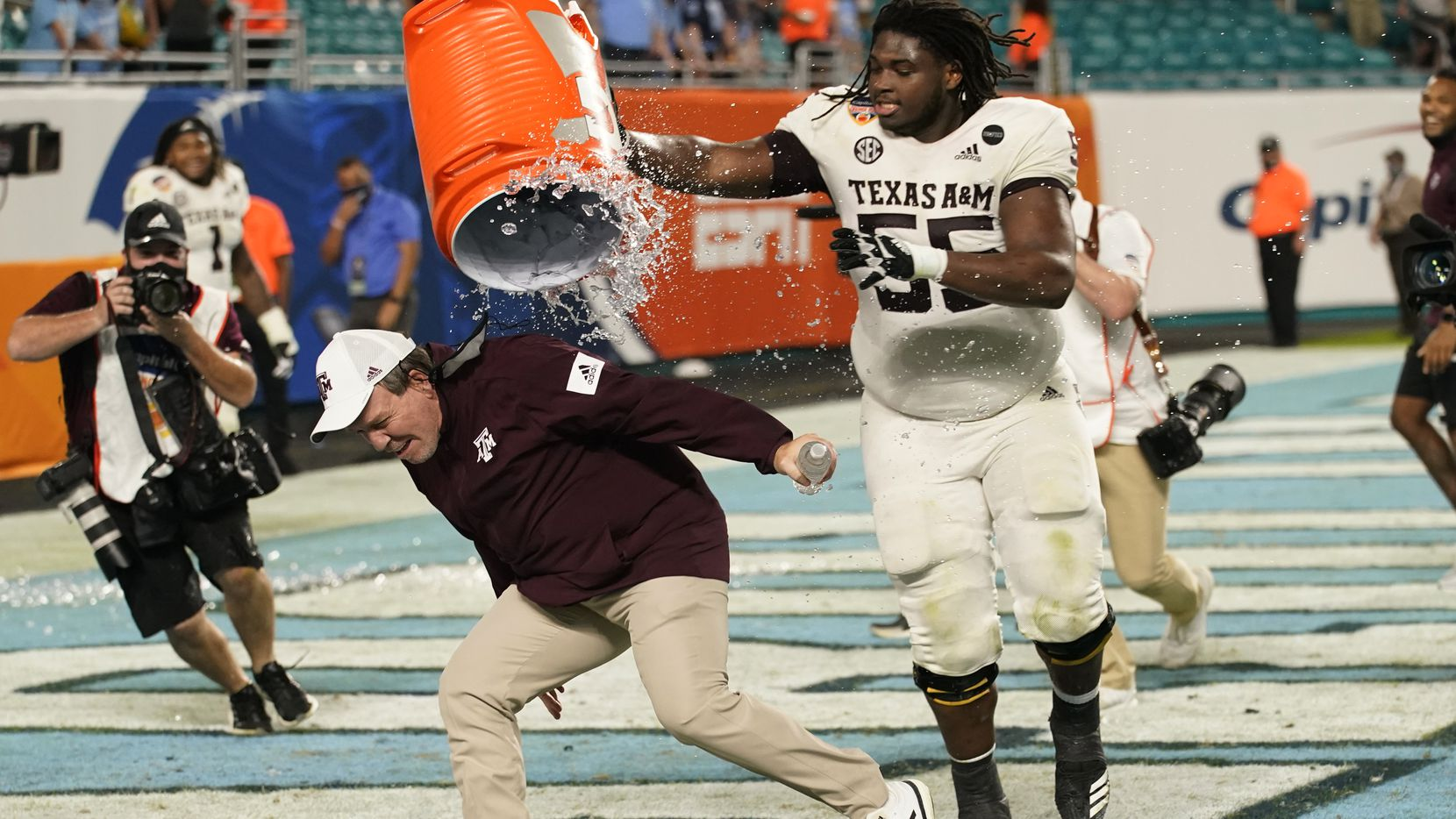 Texas A&M offensive lineman Kenyon Green (55) douses head coach Jimbo Fisher at the end of the Orange Bowl NCAA college football game, Saturday, Jan. 2, 2021, in Miami Gardens, Fla. Texas A&M defeated North Carolina 41-27.