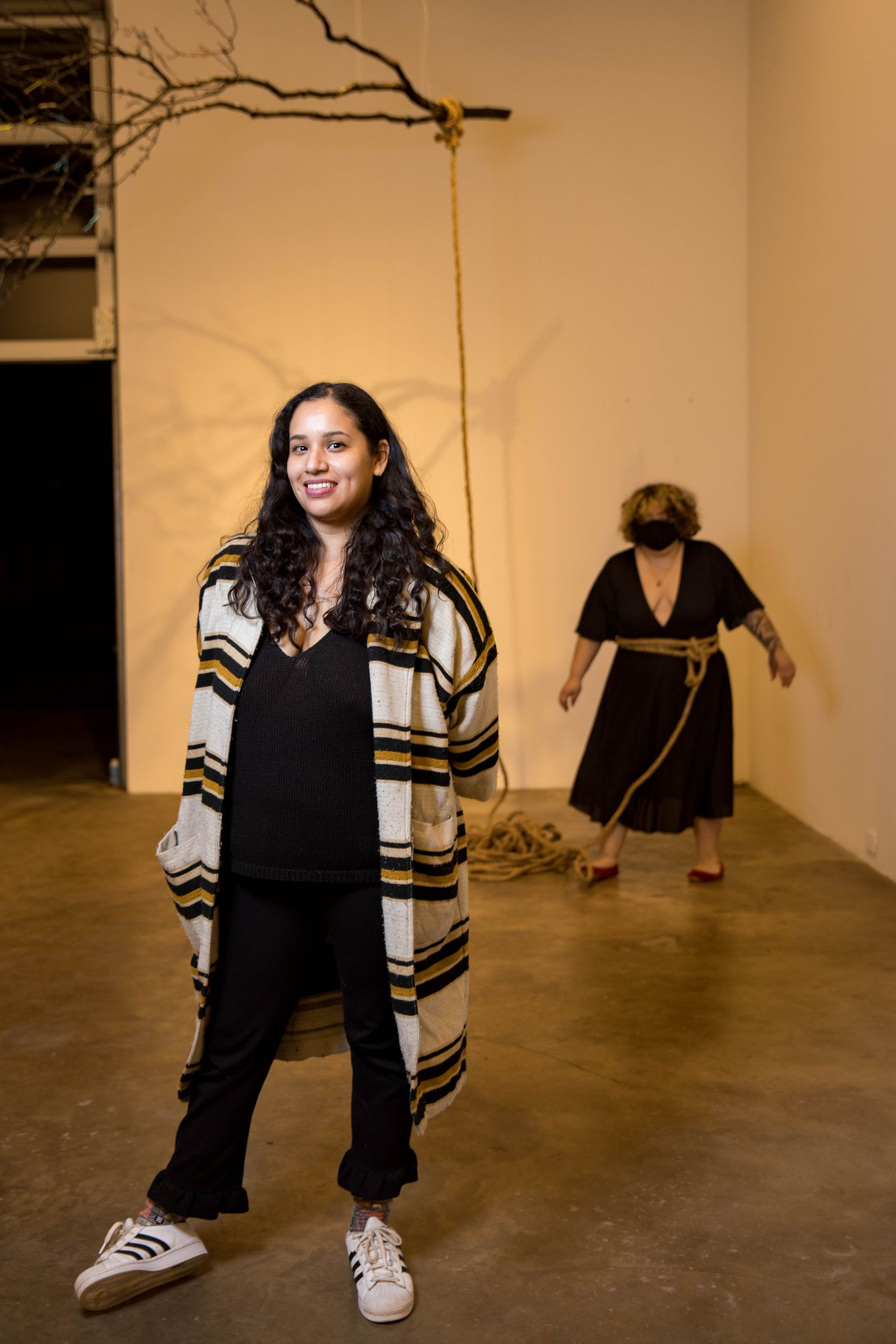 Dallas artist Christian Cruz poses for a photo in front of her piece, 'Piñata Dance' performed by Amy Zapien, at Ex-Ovo in Dallas.