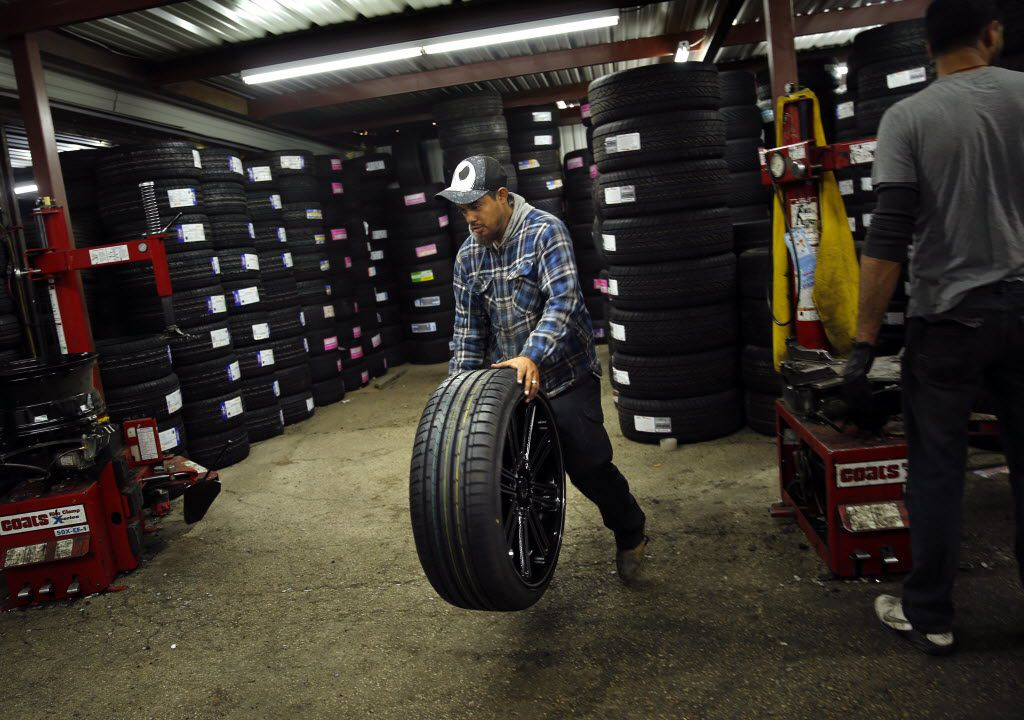 Carlo Herrera bounces a freshly filled tire on the ground after mounting it on a new rim for a customer at Omar's Wheels and Tires, the shop targeted in an anti-Muslim attack in 2015.