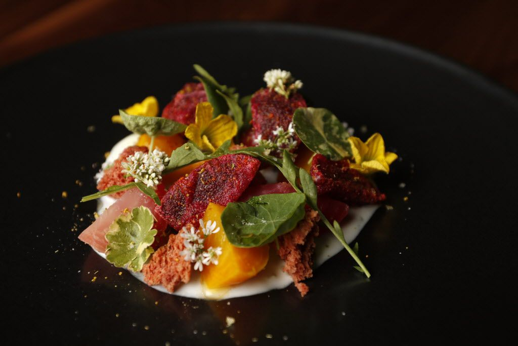 Roasted beets with Skyr yogurt, bitter greens and local honey is garnished with edible flowers.
