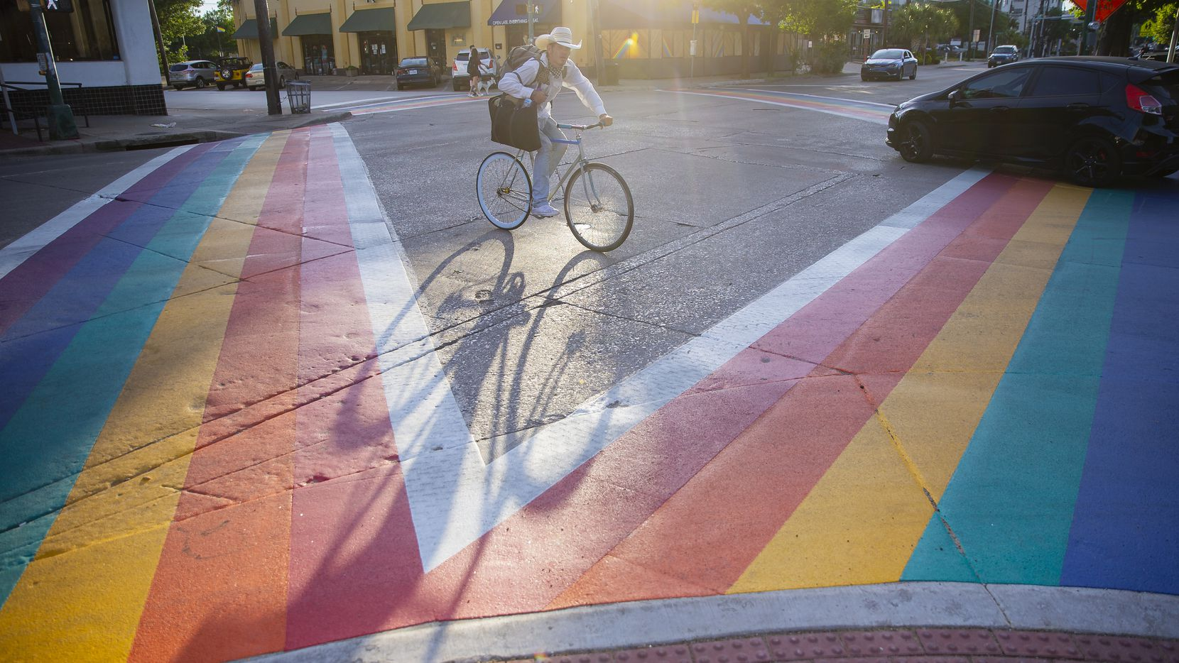 A cyclist bikes past the new rainbow crosswalks on Cedar Springs and Throckmorton St. in Oak Lawn on May 1, 2020.