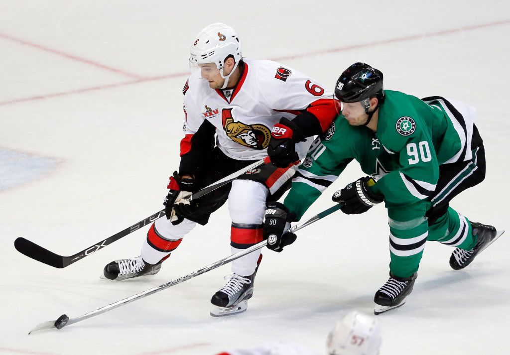 Dallas Stars center Jason Spezza (90) reaches in to take control of the puck from Ottawa Senators' Chris Wideman (6) in the third period of an NHL hockey game in Dallas, Wednesday, March 8, 2017. (AP Photo/Tony Gutierrez)