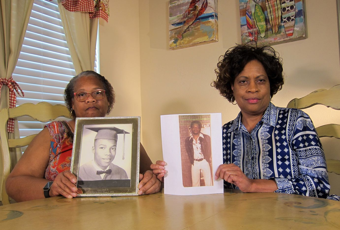In this Wednesday, April 10, 2019, photo Mylinda Byrd Washington, 66, left, and Louvon Byrd Harris, 61, hold up photographs of their brother James Byrd Jr. in Houston. James Byrd Jr. was the victim of what is considered to be one of the most gruesome hate crime murders in recent Texas history.