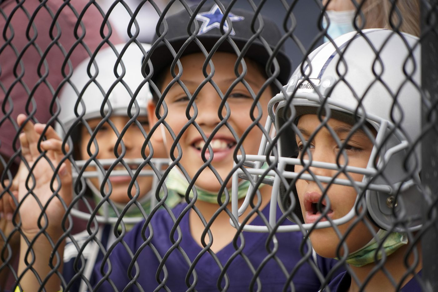 Dallas Cowboys fans press against a fence to watch a practice at training camp on Sunday, July 25, 2021, in Oxnard, Calif.