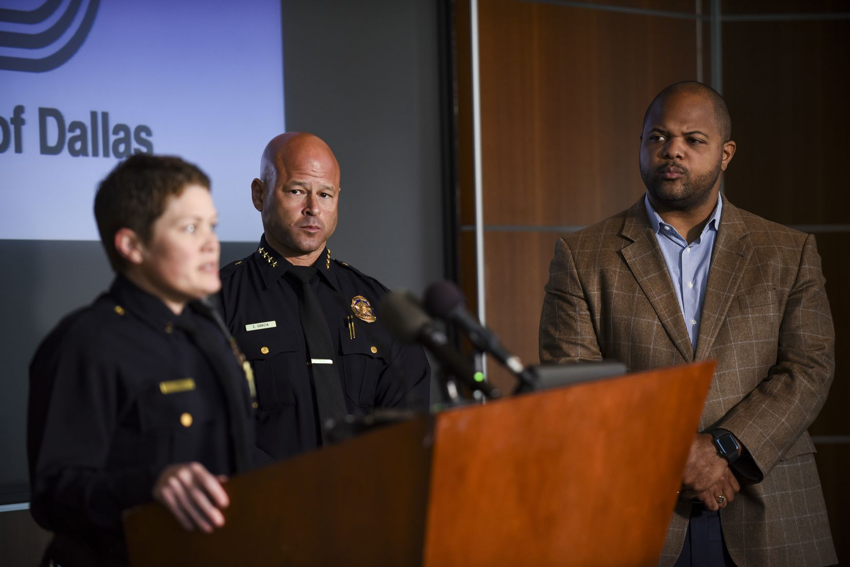 From left, Dallas Police Department Chief, Eddie Garcia and Mayor Eric Johnson peer at Dallas Police Head of Domestic Violence, Lt. Kylee Hawks, as she makes a statement during a press conference about the Dallas Police Department's plan to reduce domestic violence at the Jack Evans Police Headquarters in Dallas, Texas on Monday, October 11, 2021. (Emil Lippe/Special Contributor)