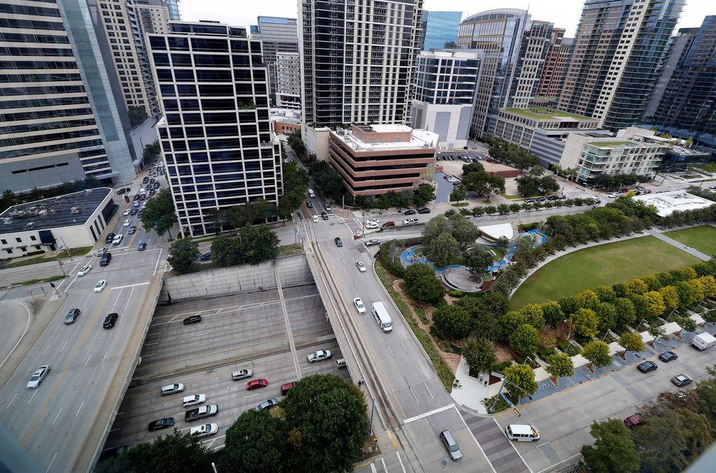 The Klyde Warren Park (right) is expanding one block to the west of St. Paul St. to accommodate some parking and a pavilion in downtown Dallas.  This overhead view shows the current opening with traffic flowing on Woodall Rodgers Freeway between Akard St. (left) and St. Paul St, Thursday, October 18, 2018. The central feature of the planned 1.2-acre, $76 million expansion is a two-story, 16,000- to 20,000-square-foot pavilion. (Tom Fox/The Dallas Morning News)