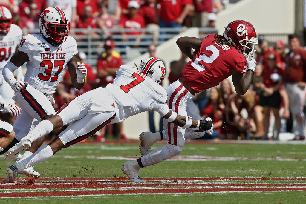 Oklahoma wide receiver CeeDee Lamb (2) avoids a tackle by Texas Tech defensive back Adrian Frye (7) in the second quarter of an NCAA college football game in Norman, Okla., Saturday, Sept. 28, 2019.