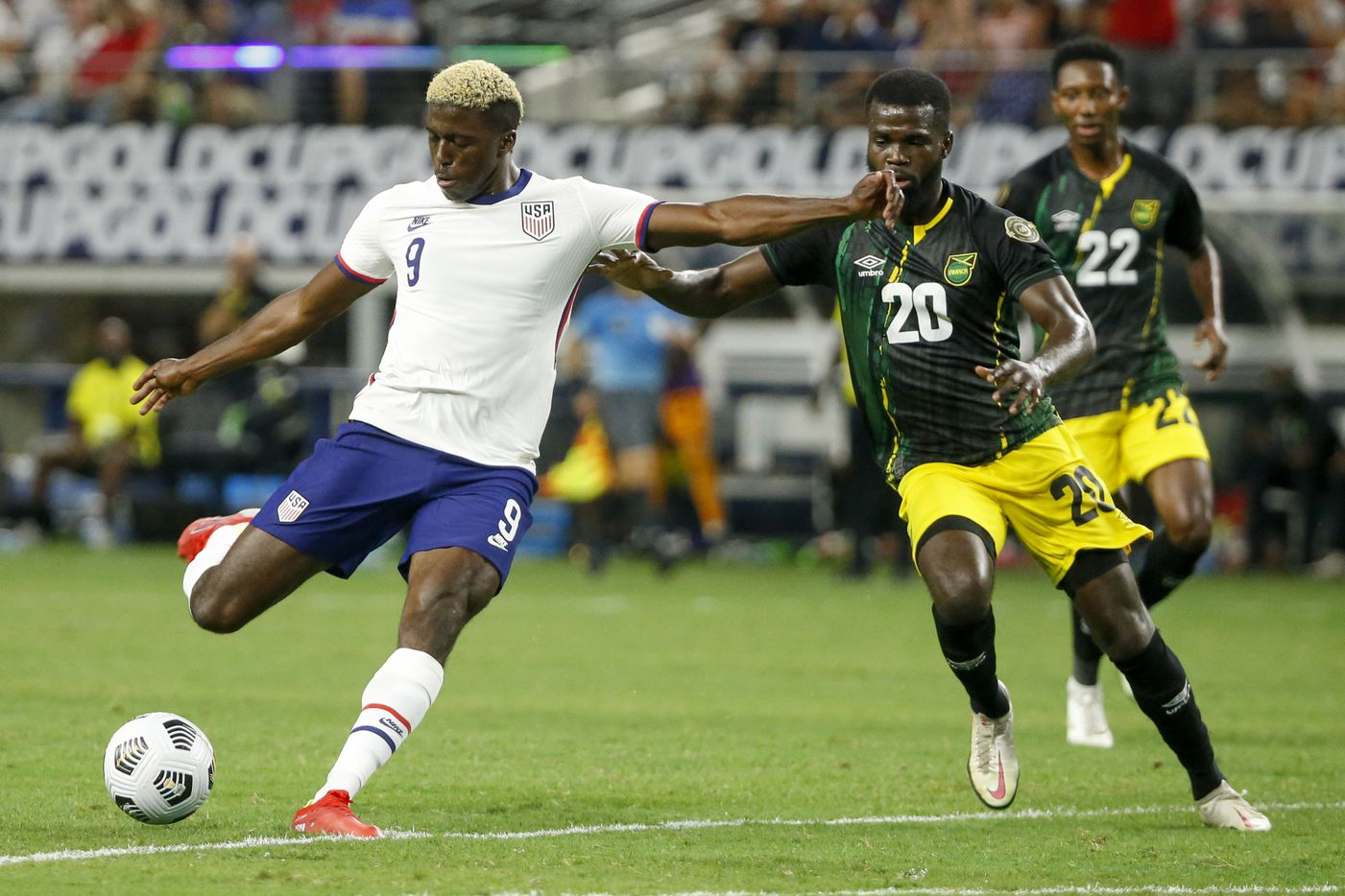 USA forward Gyasi Zardes (9) shoots the ball ahead of Jamaica defender Kemar Lawrence (20) during the second half of a CONCACAF Gold Cup quarterfinal soccer match at AT&T Stadium on Sunday, July 25, 2021, in Arlington. (Elias Valverde II/The Dallas Morning News)