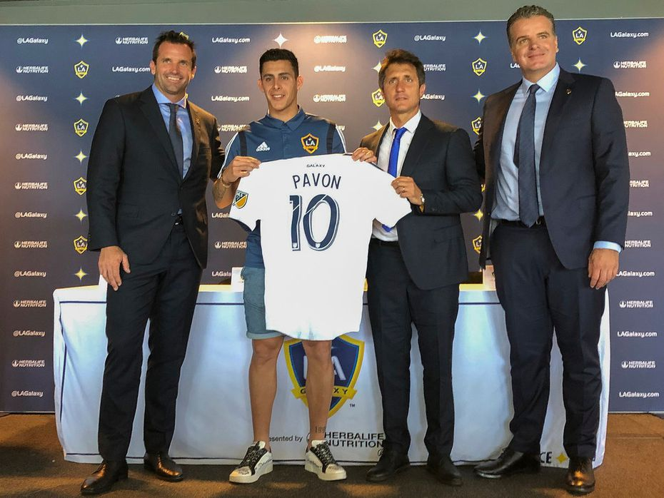 Forward Cristian Pavón, second from left, of Argentina, holds up his new LA Galaxy jersey at Dignity Health Sports Park in Carson, Calif., Thursday, Aug. 8, 2019. Standing alongside Pavon, Galaxy President Chris Klein, left, head coach Guillermo Barros Schelotto, second from right, and general manager Dennis te Kloese. The LA Galaxy acquired Pavón on loan from Argentina's Boca Juniors this week in one of the biggest player acquisitions in recent Major League Soccer history. (AP Photo/Greg Beacham)