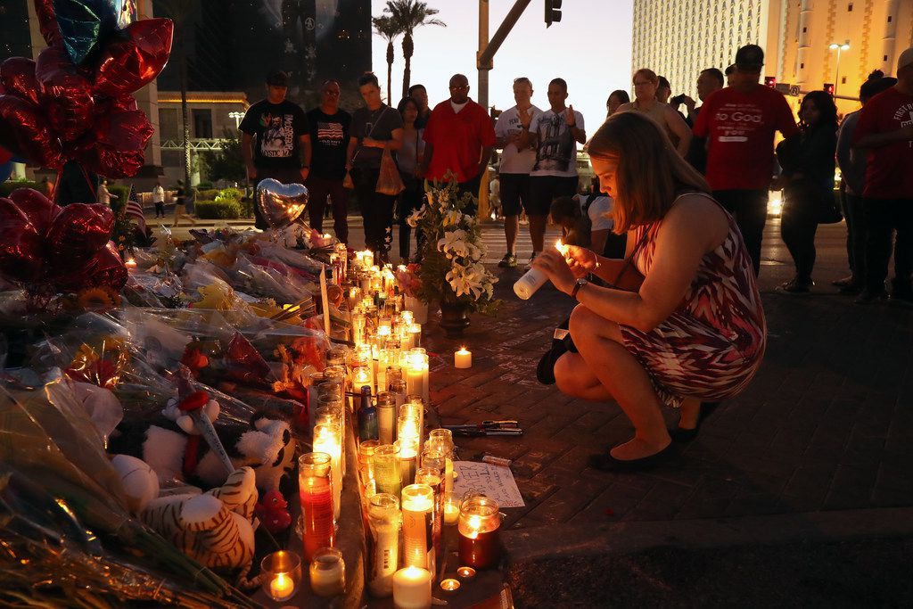A woman lights a candle on Oct. 4 at a sidewalk memorial to victims of the mass shooting.