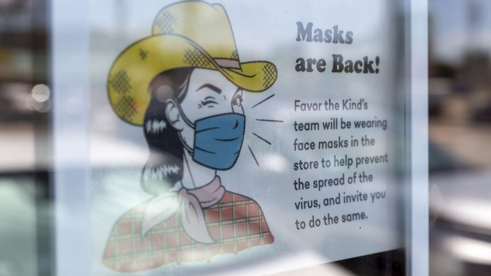 A sign at Favor the Kind on North Henderson in Dallas encourages customers to wear face masks. Masks are required in schools and businesses after a new executive order from Dallas County Judge Clay Jenkins.