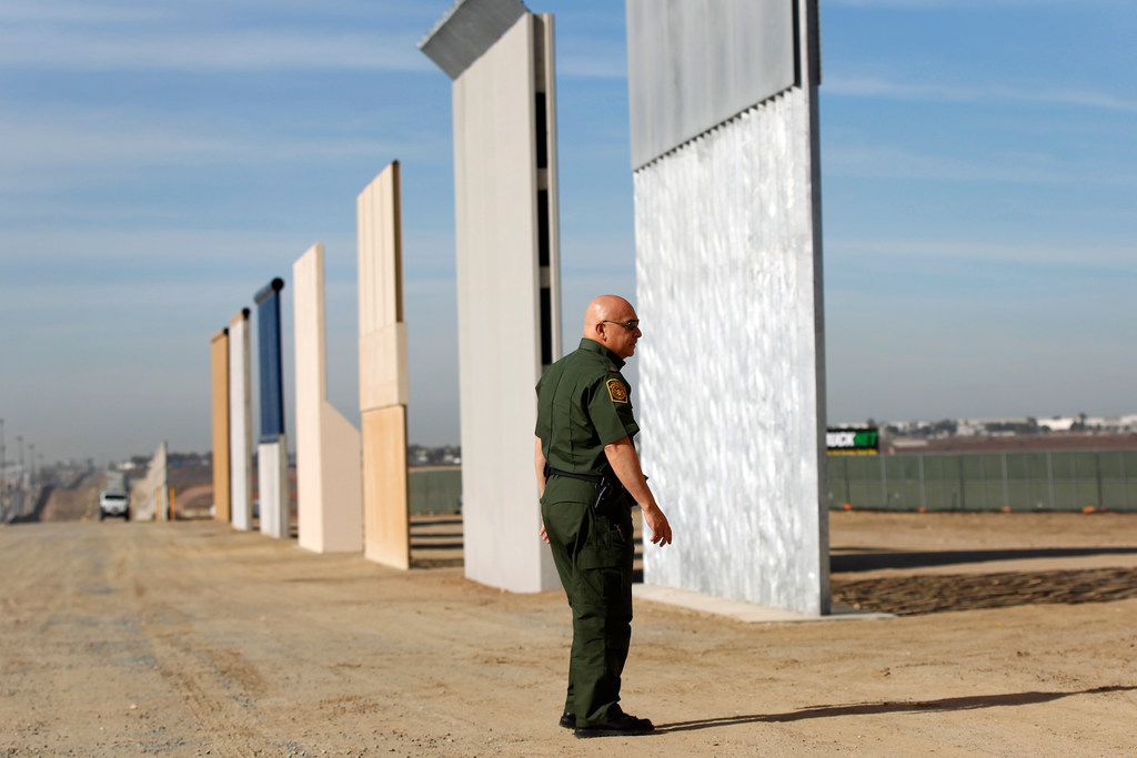 Mario Villarreal, the field office division chief for Customs and Border Protection, walks near border wall prototypes that were built east of San Ysidro on the border with Mexico on Nov. 20, 2017. (K.C. Alfred/San Diego Union-Tribune/TNS)