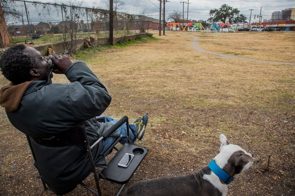 "Charlie Alexander Jr., who is homeless, took a sip of beer on Dec. 12 while his dog King sat by his side on the lot where the future Vickery Meadow library will be built. Alexander picks up the trash that is littered on the lot daily.  ""Since I am out here I thought, 'Hell ,I will give back,'"" he said."