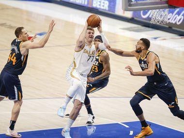 Dallas Mavericks guard Luka Doncic (77) attempts a shot as Utah Jazz forwards Bojan Bogdanovic (44), Royce O'Neale (23) and Rudy Gobert (27) defendduring the second half of an NBA basketball game in Dallas, Monday, April 5, 2021.