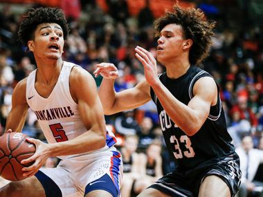 Duncanville junior guard Micah Peavy (5) looks for room against Denton Guyer junior Eli Stowers (33) during the first half of the Class 6A Region I championship boys basketball game at the Wilkerson-Greines Athletic Center in Fort Worth, Saturday, March 2, 2019. Duncanville won 66-62 in overtime. (Brandon Wade/Special Contributor)