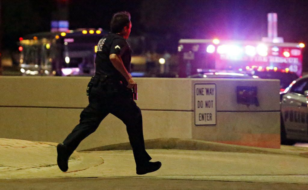 A Dallas police officer runs with his gun drawn during the chaos that followed a deadly shooting  Friday, July 7, 2016 in Dallas. G.J. McCarthy/Staff Photographer
