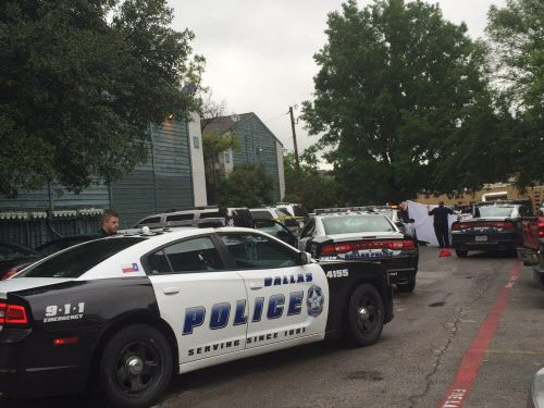 Dallas police held up a sheet as they removed the body from a car at the Winding Way Apartments in North Dallas on April 23. The apartments are sandwiched between three of the city's designated high-crime zones.