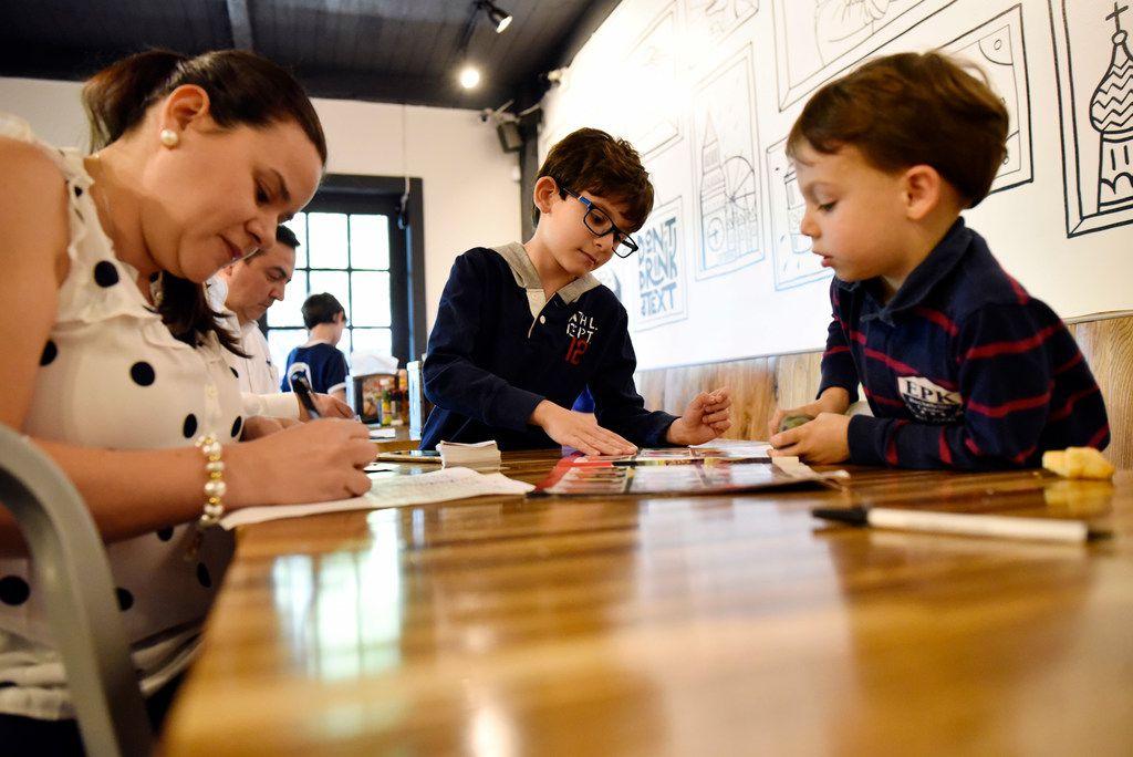 Juliana Rodriguez, left, works with her son Nicolas Lamus, 7, and Sebastian del Porto, 4, as they organize Panini stickers.