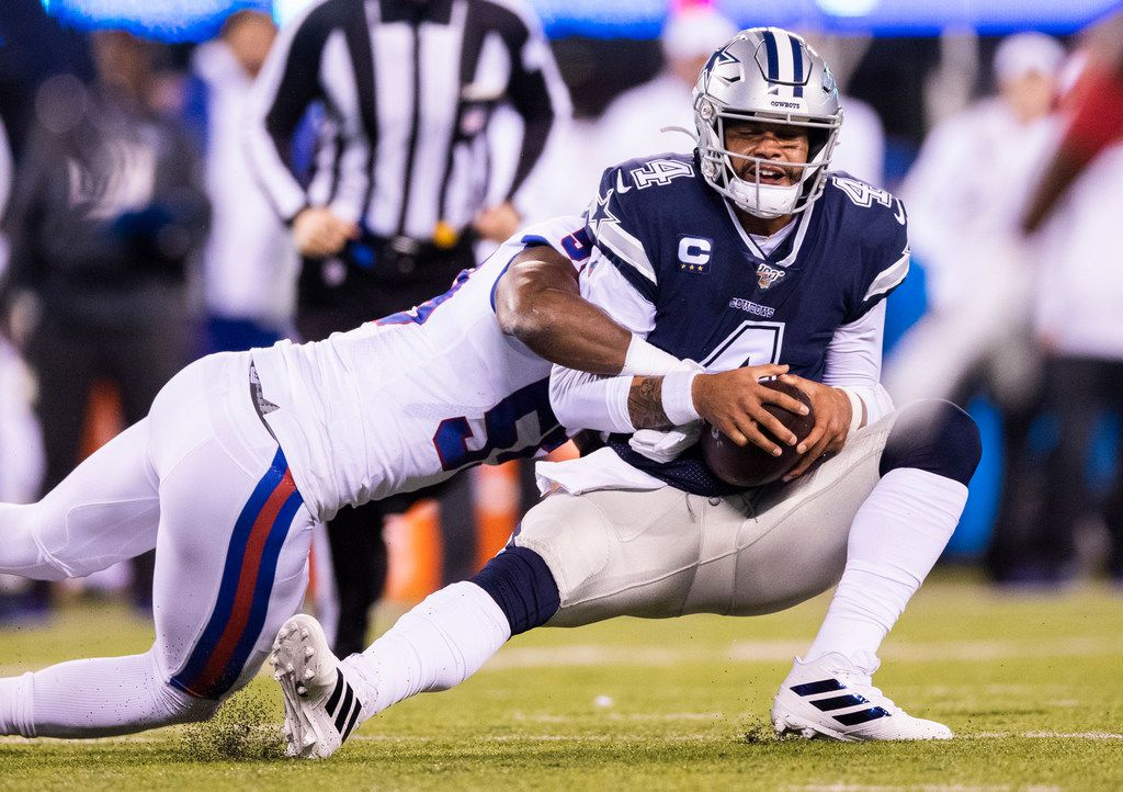 Dallas Cowboys quarterback Dak Prescott (4) is tackled by New York Giants linebacker Lorenzo Carter (59) after fumbling and recovering a snap during the first quarter of an NFL game between the Dallas Cowboys and the New York Giants on Monday, November 4, 2019 at MetLife Stadium in East Rutherford, New Jersey.