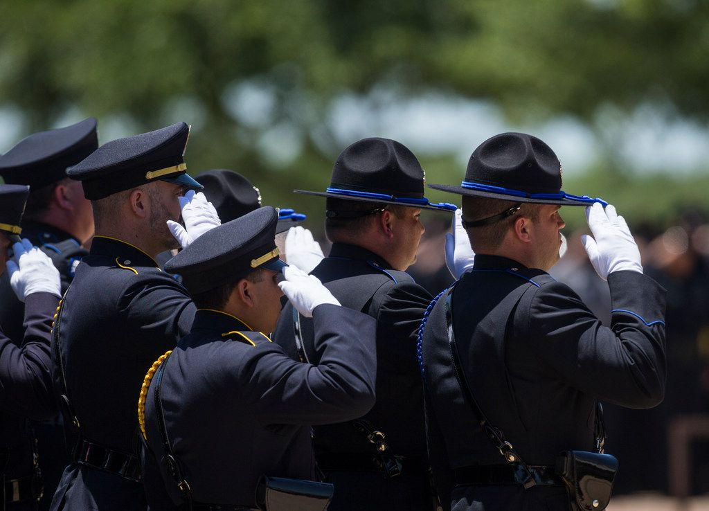 Police salute the casket of their fallen colleague A.J. Castaneda outside The Potter's House church in Dallas.