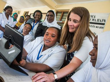 Nurse Chesca Mbilinyi and Melinda Gates try the new digital system to find records of patients in the Magomeni Health Center in Dar Es Salam, Tanzania, on June 29, 2016. ORG XMIT: RG477662