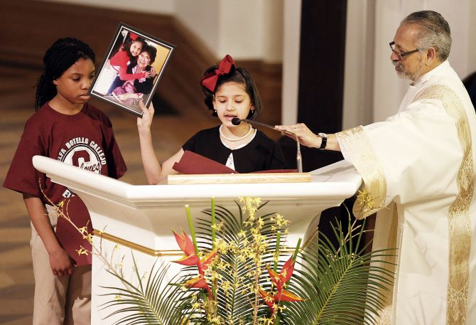 Adelfa Botello Callejo Elementary School students Lois Enganamoulouk and Noemi Sosa spoke at Callejo's funeral Mass on Thursday. Noemi holds a photo of herself and Callejo that was taken during the school's dedication last year in Pleasant Grove.