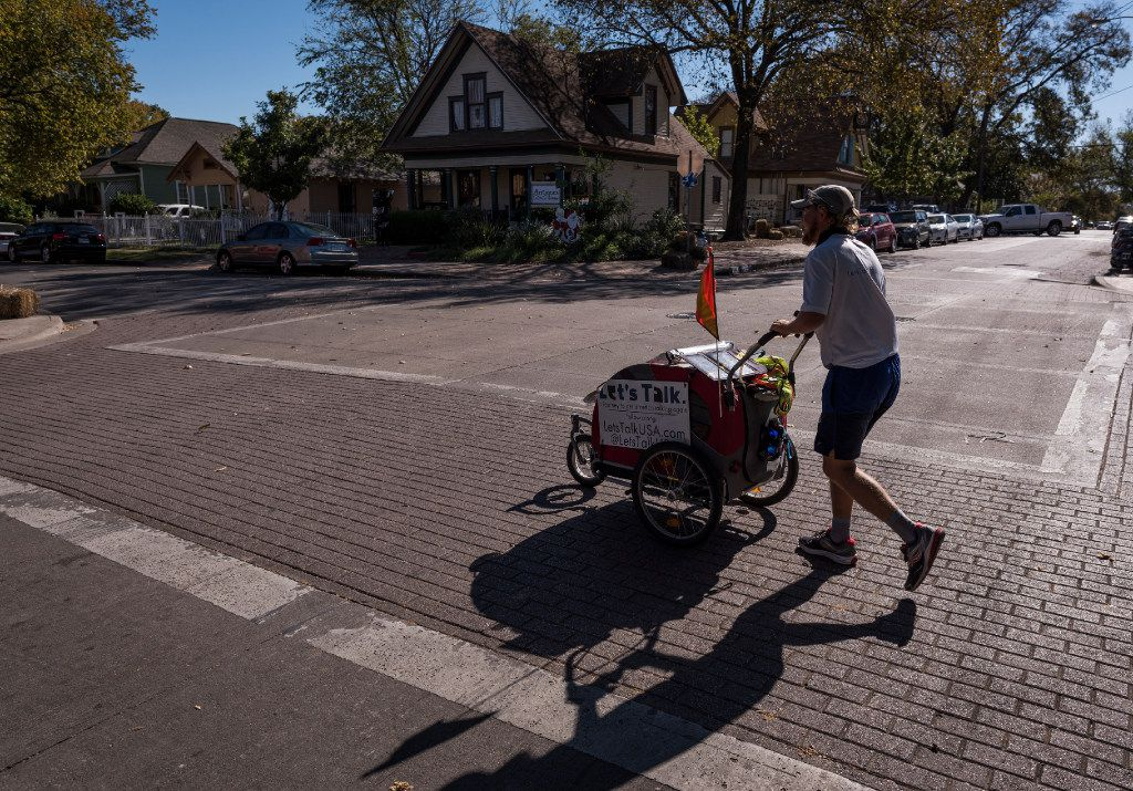 Chris Andrews, who is on a cross-country walk to promote face-to-face communication, crosses Bishop Avenue in Bishop Arts in Dallas on Monday.