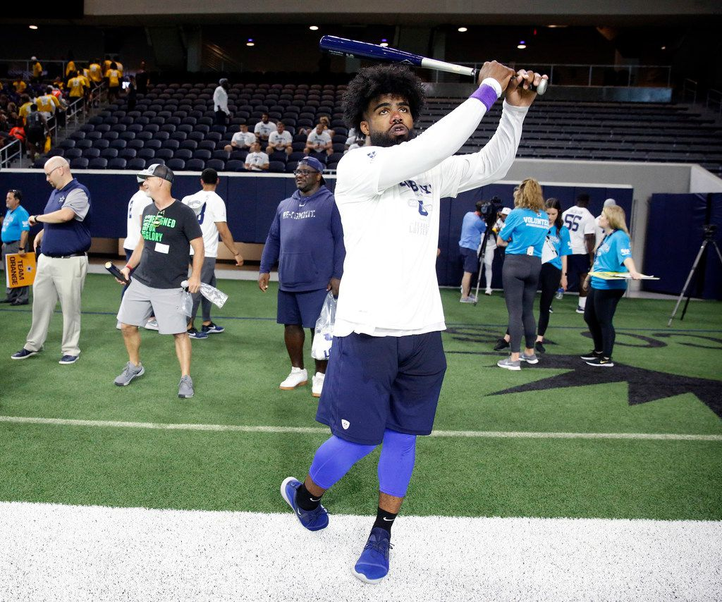 Dallas Cowboys running back Ezekiel Elliott practices his home run swing during the Cowboys U high school football tournament in the Ford Center at The Star in Frisco, Texas, Thursday, June 6, 2019. Elliott plans on participating in Dirk Nowitzki's Heroes Celebrity Baseball Game Friday. Cowboys players served as coaches to select high school players during the football camp. The Dallas-Fort Worth student-athletes were selected by their respective high school football coaches and district athletic directors to attend the camp. The nearly 200 students represent 52 North Texas high schools from 12 different school districts. (Tom Fox/The Dallas Morning News)