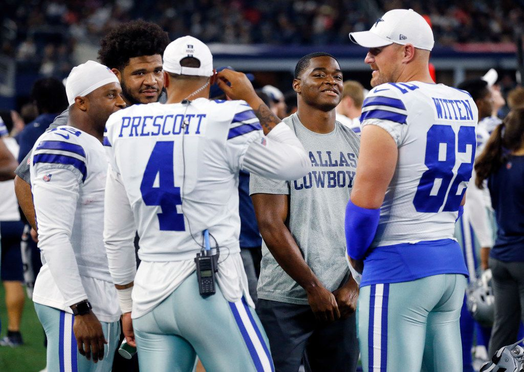 Dallas Cowboys tight end Jason Witten (82), wide receiver Amari Cooper (19), quarterback Dak Prescott (4), center Joe Looney (73) and wide receiver Randall Cobb (18) visit on the sideline during the second half of their preseason game against the Tampa Bay Buccaneers at AT&T Stadium in Arlington, Texas, Thursday, August 29, 2019. None of the players played tonight.