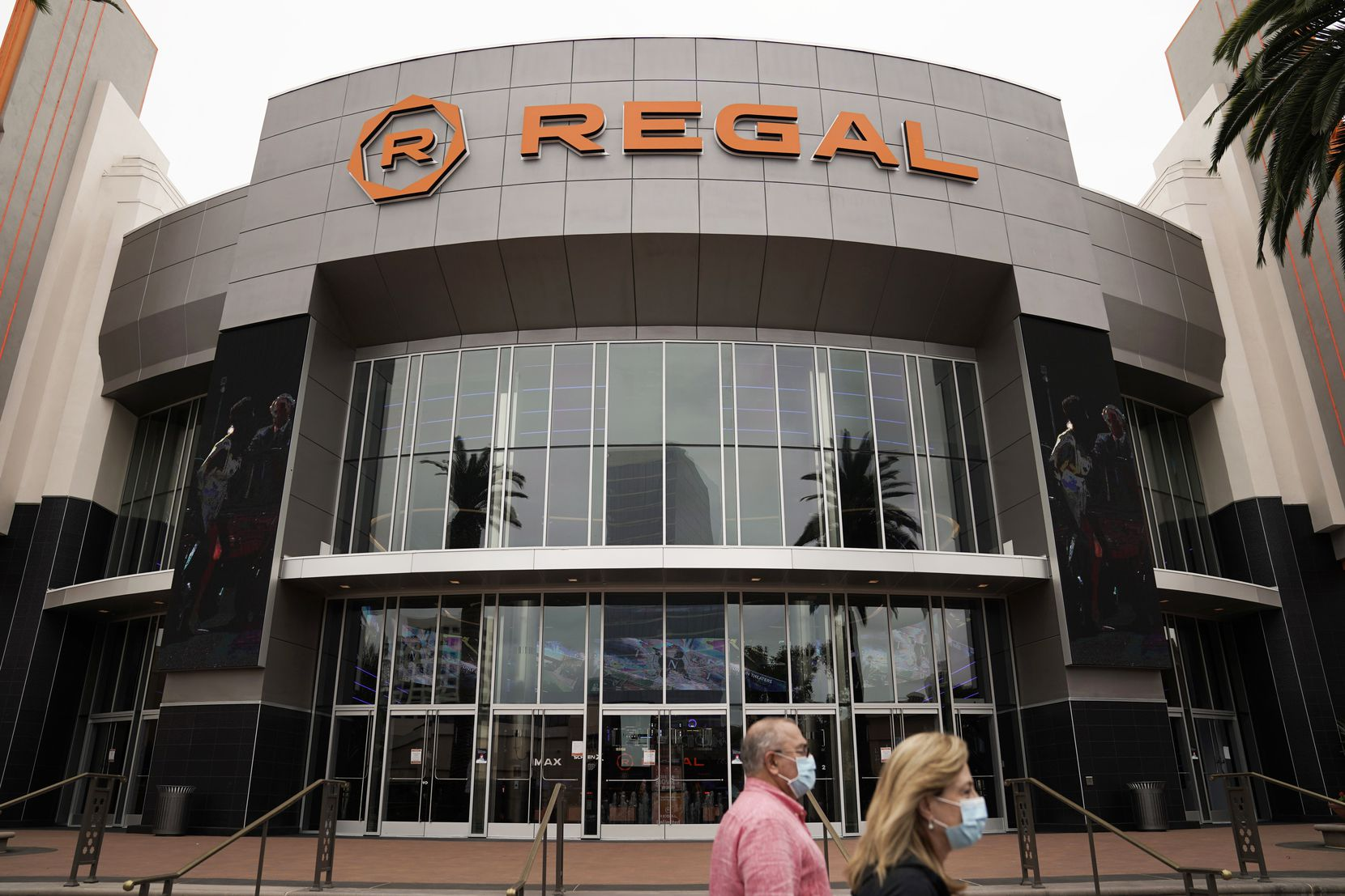 Two shoppers walk past a Regal movie theater in Irvine, Calif. in September.