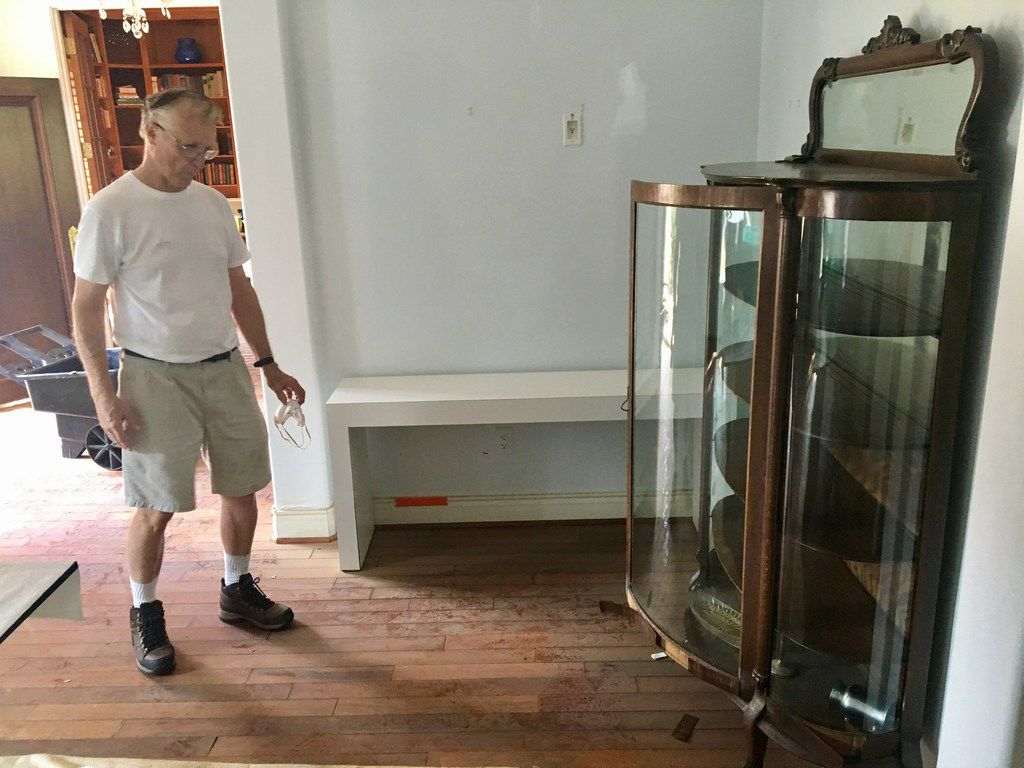 Arthur Storey, the former head of the Harris County Flood Control District, looks at a flood-ruined family heirloom from the 1800s at his home in Memorial Drive Acres in Houston on Sept. 9, 2017. (Naomi Martin/ Staff)