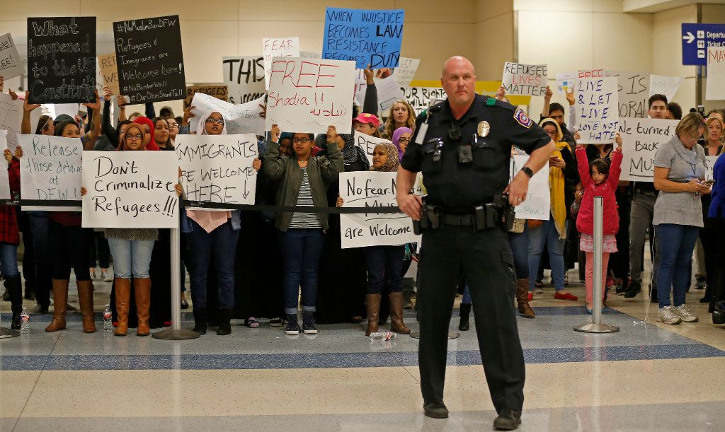 Airport police stand guard as the number of protesters at DFW Internation Airport swelled from dozens to hundreds to more than 1,000 on Saturday.