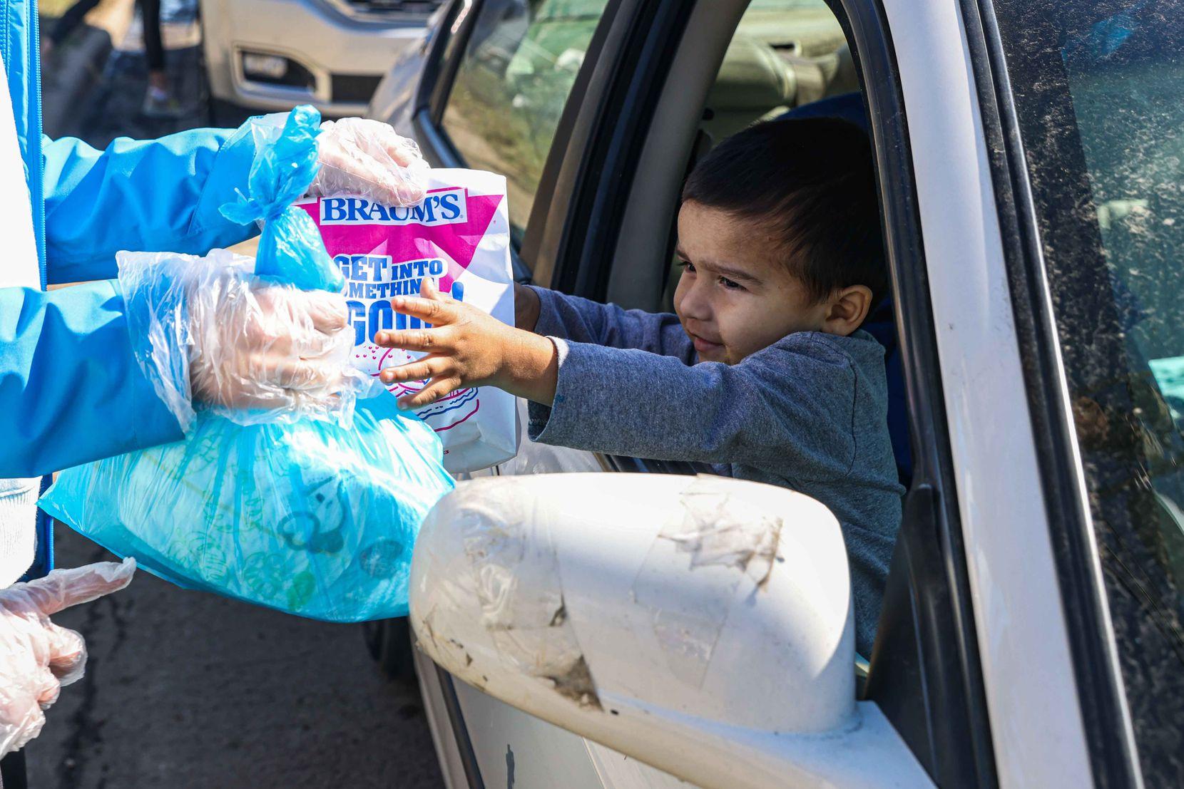 Adolfo Chavarria, 3, received food aid from volunteer Rachel Harper, 15, at the Ledbetter food pantry in Iglesia El Calvario on Friday.