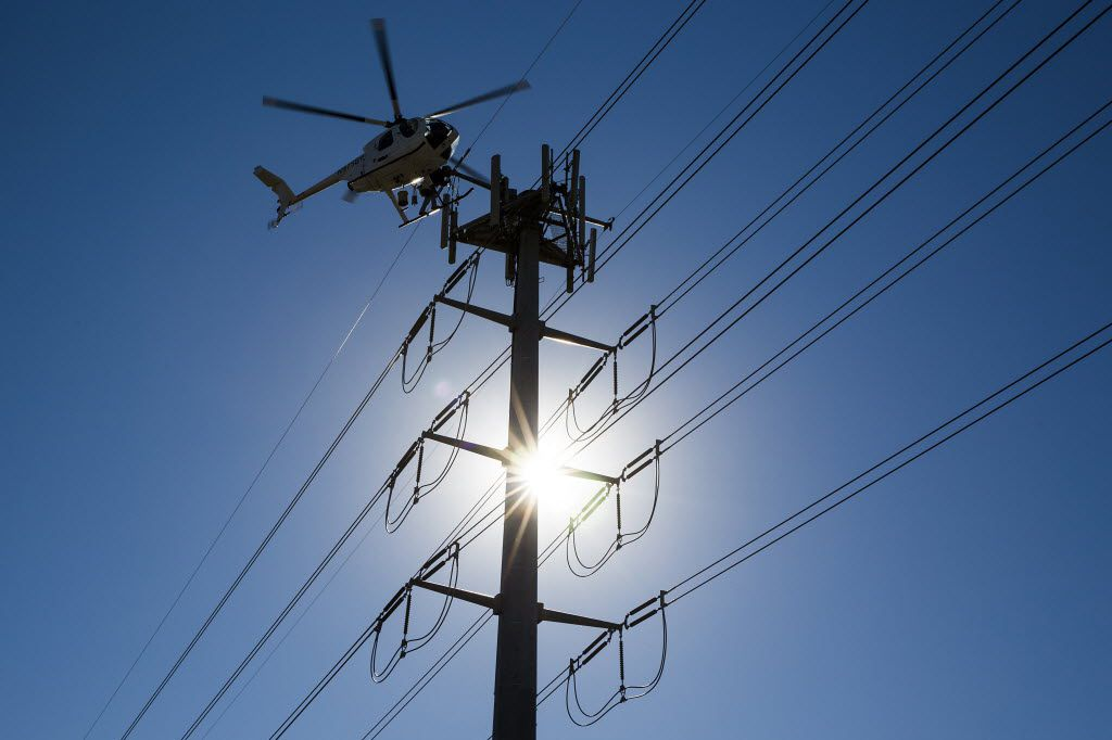 Helicopter linemen for an Oncor contractor work on transmission lines near Royal Lane at Central Expressway on Friday, Jan. 15, 2016, in Dallas.   Oncor Electic Delivery is using linemen in helicopters to upgrade electric towers . (Smiley N. Pool/The Dallas Morning News)