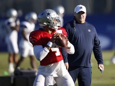 Cowboys head coach Mike McCarthy watches while quarterback Dak Prescott (4) runs through a drill during training camp at The Star in Frisco on Thursday, Aug. 20, 2020.