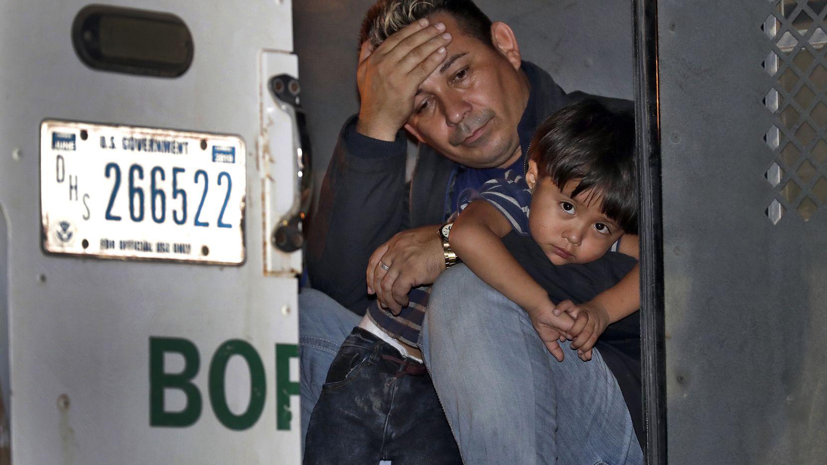 Un padre y su hijo de 3 años se asoman a la puerta de un vehículo de la Patrulla Fronteriza en el que están detenidos, el miércoles 18 de julio de 2018 en San Luis, Arizona.