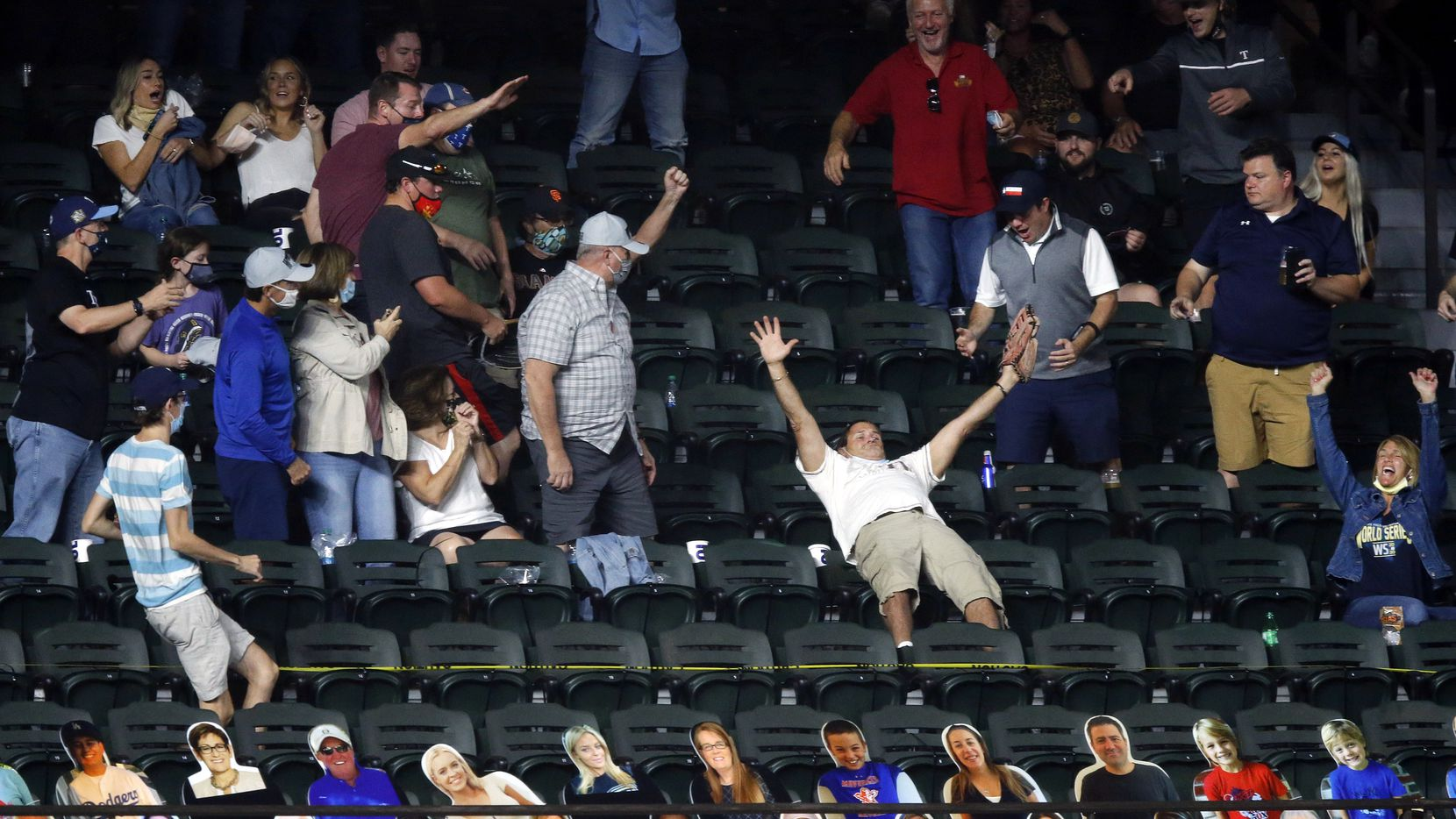 A fan (arms extended) in left field catches Los Angeles Dodgers designated hitter Will Smith's solo home run against the Tampa Bay Rays during the sixth inning in Game 2 of the World Series at Globe Life Field in Arlington, Wednesday, October 21, 2020. (Tom Fox/The Dallas Morning News)