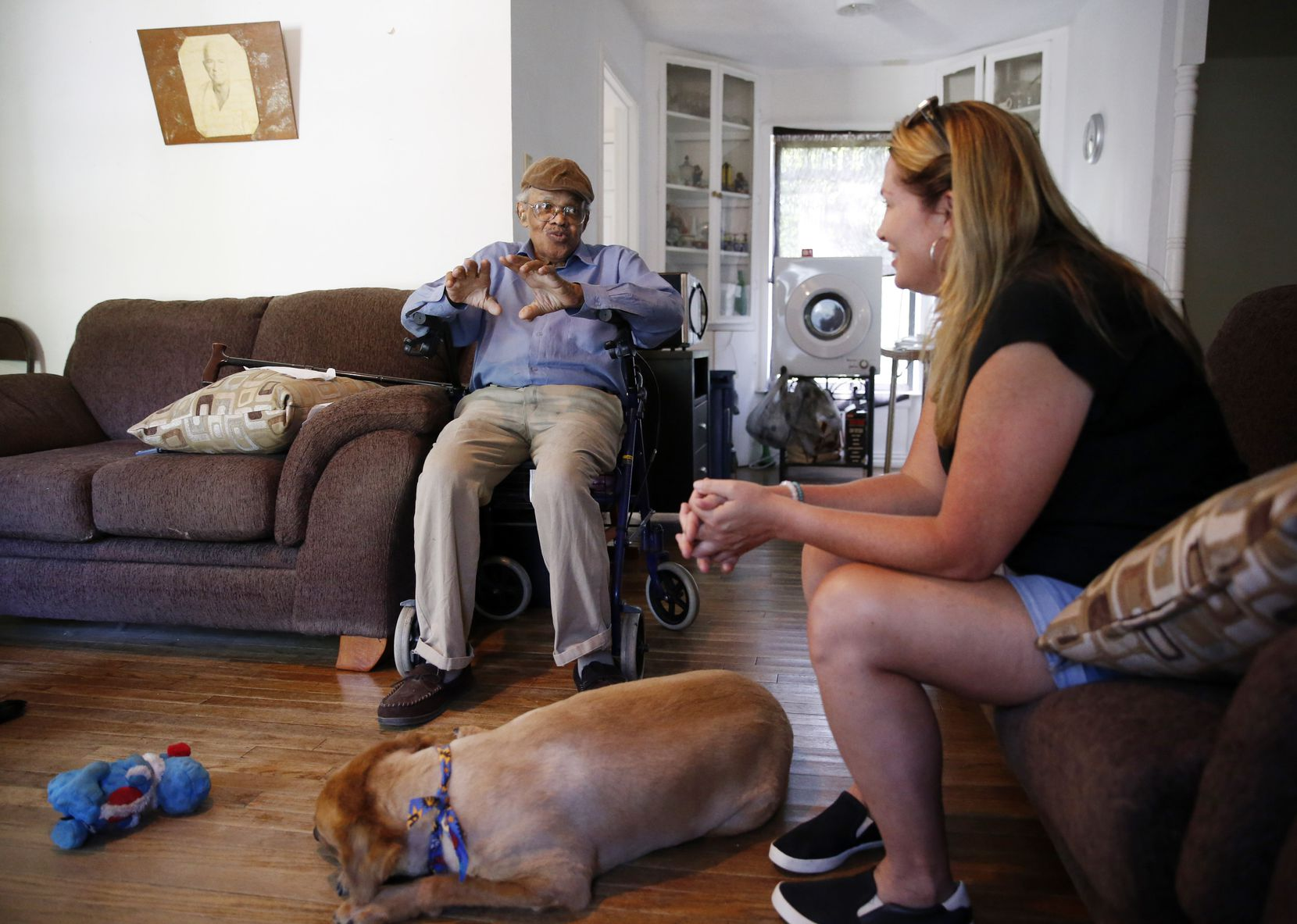 James Evans, 83, talks with Jeanne Marie Boyne (right), a volunteer for the Seniors' Pet Assistance Network as Renny rests on the floor at his home in Dallas, on Saturday, July 13, 2019.