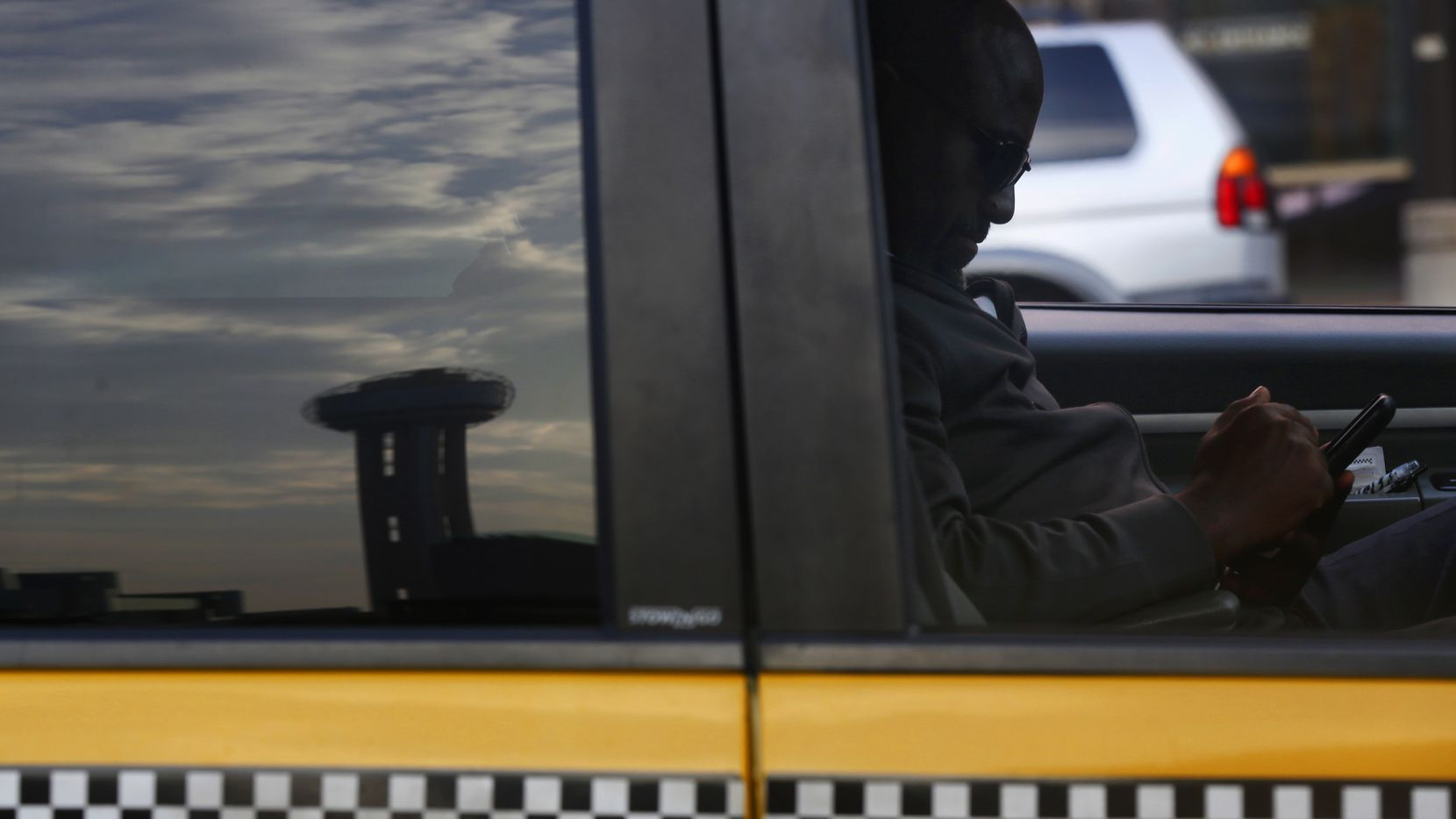 A Yellow Cab driver checked his phone while he waited in front of the Omni Hotel in Dallas in 2013. Yellow Cab's parent company Irving Holdings, three executives and several related entities have to pay the U.S. $1.125 million to resolve Medicaid fraud allegations. (Nathan Hunsinger/The Dallas Morning News File Photo)