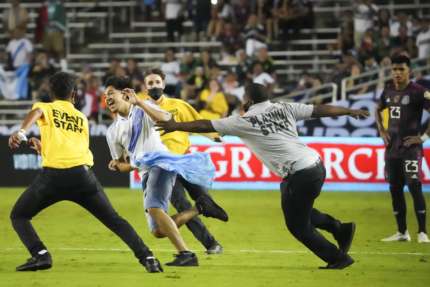 Security guards chase a fan carrying a Guatemala flag as he runs onto the field past Mexico midfielder Jesús Gallardo (23) during the second half of a CONCACAF Gold Cup Group A soccer match at the Cotton Bowl on Wednesday, July 14, 2021, in Dallas.
