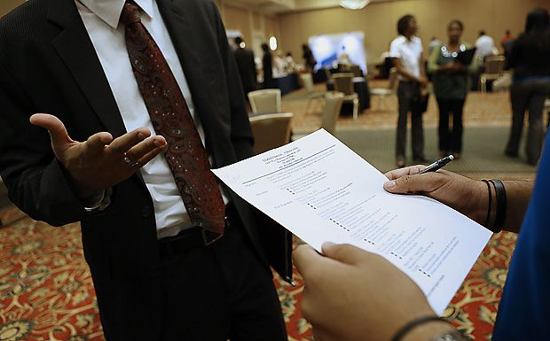 A recruiter, right, reviews a job seeker's resume during a Coast to Coast Career Fairs event in Houston, Texas, U.S., on Tuesday, Aug. 7, 2012. The U.S. Department of Labor is scheduled to release intial jobless claims data on Aug. 9. Photographer: Aaron M. Sprecher/Bloomberg