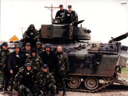 FBI tactical agents pose with one of the tanks used in the Branch Davidian siege near Waco.
