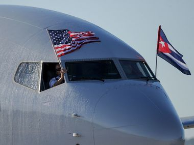 An American Airlines plane fluttering US and Cuba national flags is seen upon arrival at Jose Marti International Airport becoming the first Miami-Havana commercial flight in 50 years, coinciding with the beginning of the tributes to late Cuban leader Fidel Castro, on November 28, 2016 in Havana. (YAMIL LAGE/AFP/Getty Images)