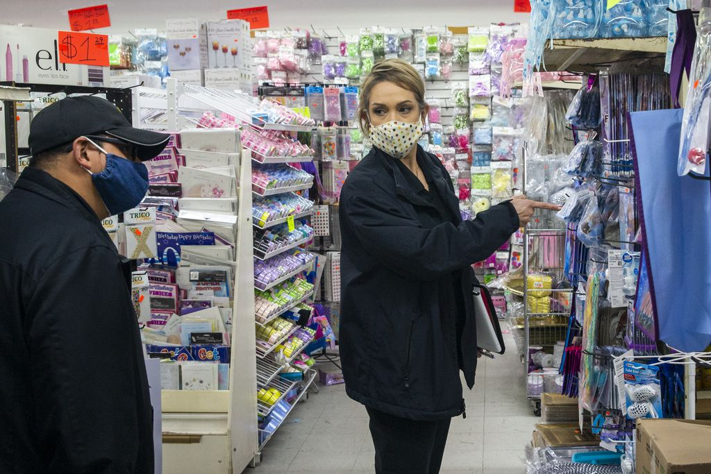 Dallas County Health and Human Services workers Marisa Gonzales and Armando Martinez inspect the $1.00 Mart store in Pleasant Grove, in southeast Dallas, for compliance with COVID-19 safety rules.