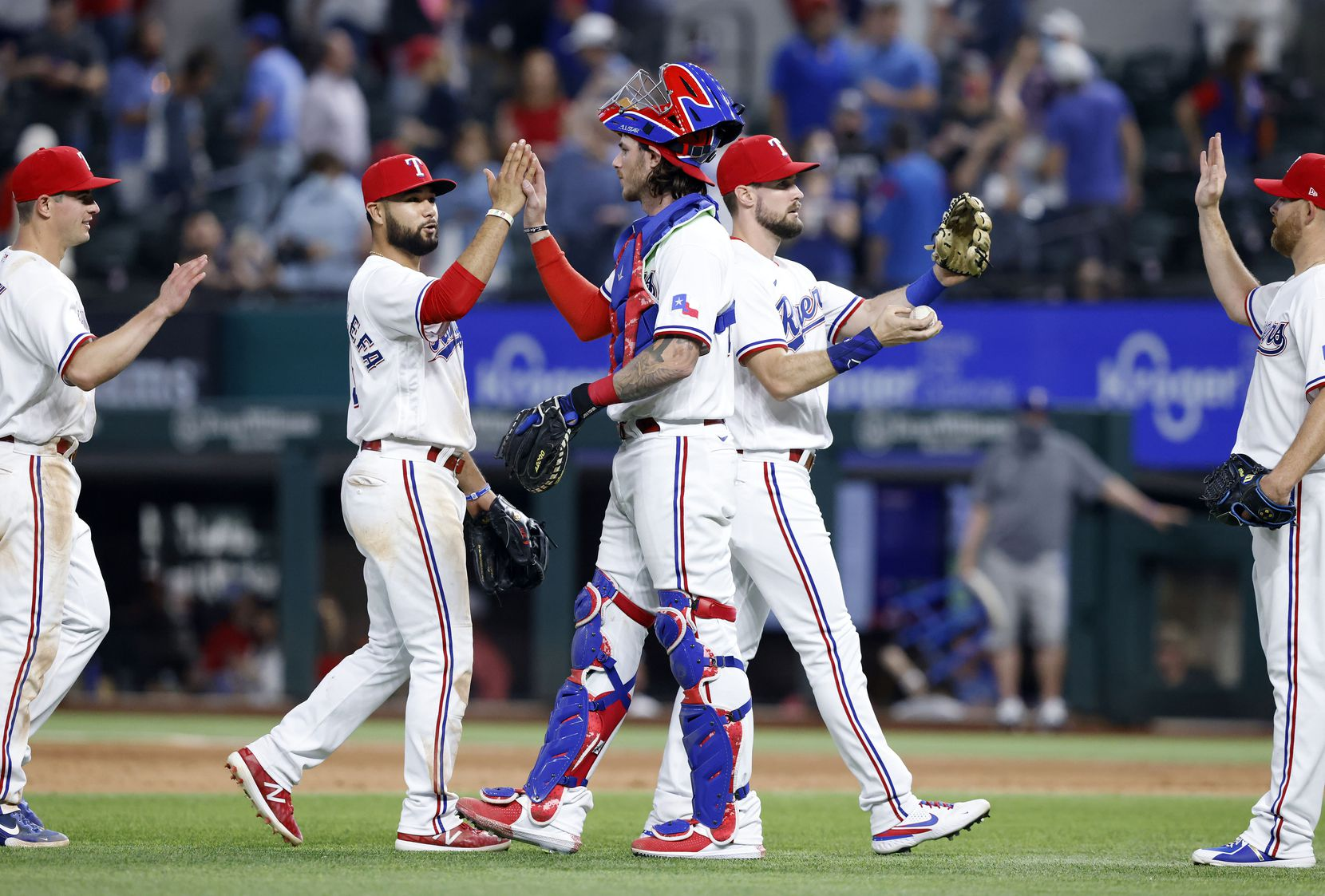 Texas Rangers catcher Jonah Heim (center) gives a high-five to teammate Isiah Kiner-Falefa after defeating the Toronto Blue Jays at Globe Life Field in Arlington, Tuesday, April 7, 2021. The Rangers won, 7-4. Heim hit his first Major League home run earlier in the game. (Tom Fox/The Dallas Morning News)