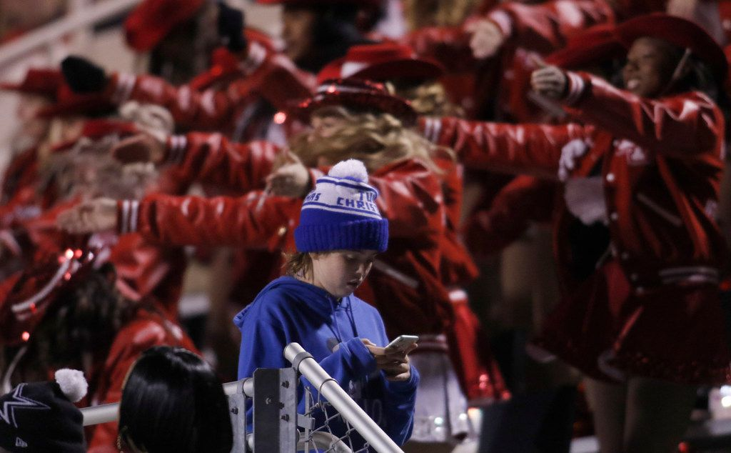 A young Lake Highlands fan uses his cellphone as members of the Lake Highlands drill team perform in the background during first quarter action of the Lake Highlands versus Richardson game. The two teams played their District 8-6A football game at Wildcat-Ram Stadium on the campus of Lake Highlands High School in Dallas on November 8, 2019. (Steve Hamm/ Special Contributor)