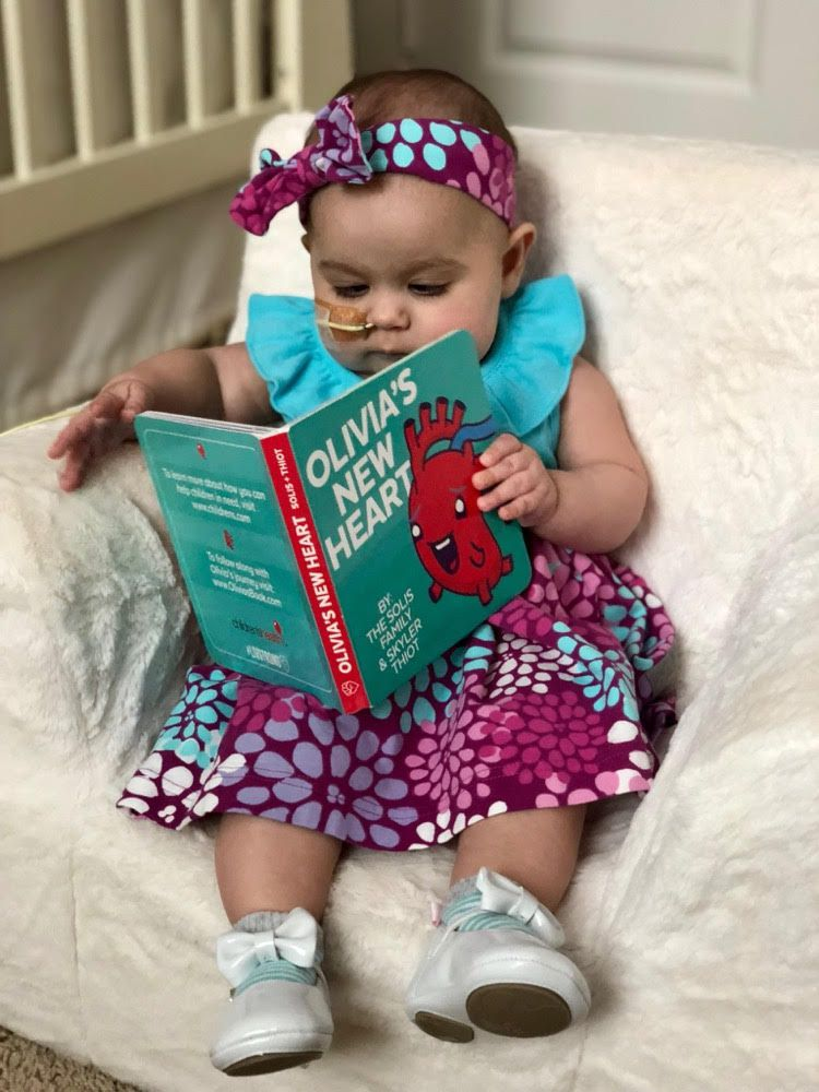 Olivia Solis at almost 8 months, with the book about her life so far