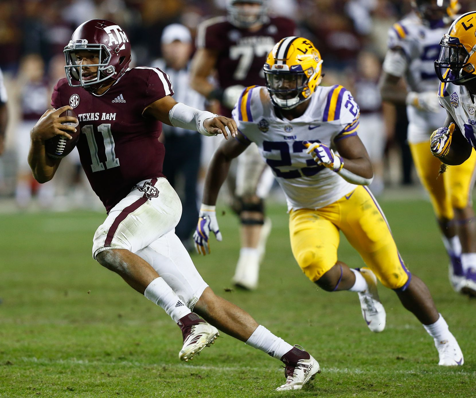 COLLEGE STATION, TEXAS - NOVEMBER 24: Kellen Mond #11 of the Texas A&M Aggies rushes past Micah Baskerville #23 of the LSU Tigers in overtime at Kyle Field on November 24, 2018 in College Station, Texas.